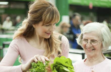 une femme aide une autre au marché